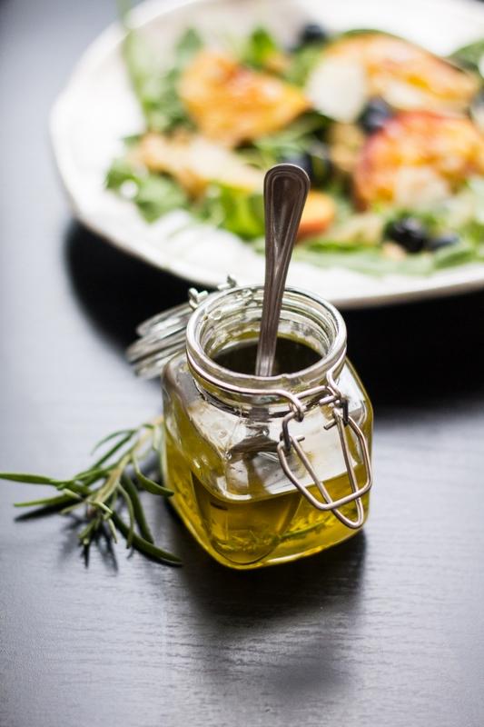 condimento per insalata d'estate (pesche, rucola, mirtilli, parmigiano) a base di olio, limone, rosmarino